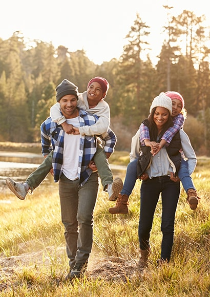 A loving family walking through nature after getting dental services Issaquah.