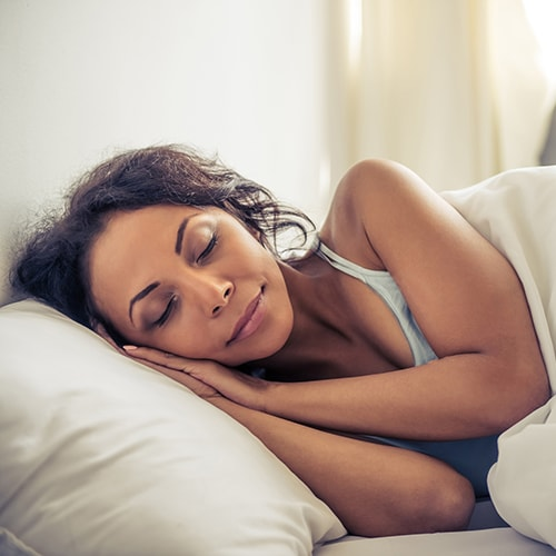 A sleeping woman getting a good night's sleep after getting sleep apnea treatment