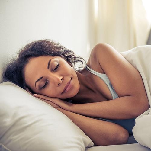 A sleeping woman getting a good night's sleep after getting sleep apnea treatment
