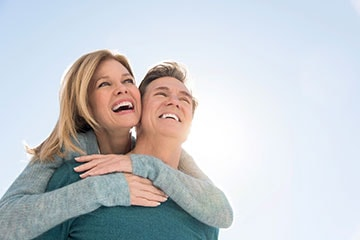 Smiling couple with healthy smiles and bodies thanks to oral systemic health