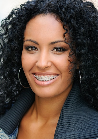 A smiling woman with braces, thanks to orthodontics