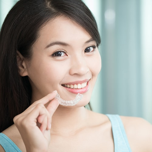 Smiling woman putting on her Invisalign aligners