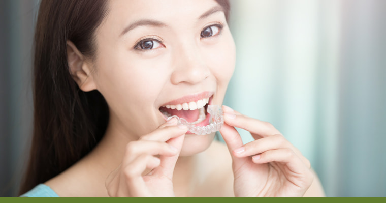 woman about to place Invisalign clear aligner on her teeth