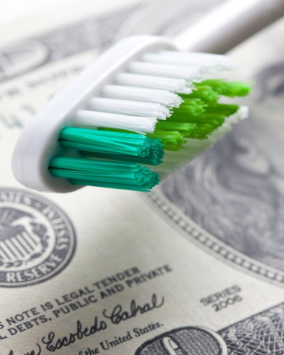 Tooth brush and $100 bill to represent the money with dental care