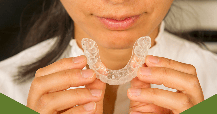 Close-up of woman's hands holding an Invisalign aligner.